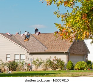 Roofers repairing the roof of a house in the suburbs.