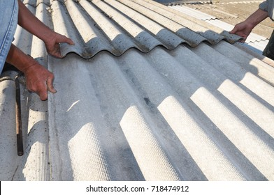Roofers replace damaged asbestos tile. Repair asbestos roof.