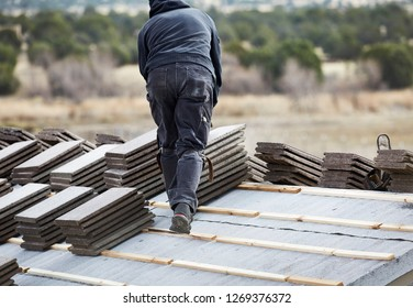 Roofers stacking cement roofing tiles on roof in preparation to lay them