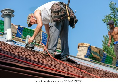 Roofers working on replacing the roof of residential building in the summer; blue sky and trees in the background