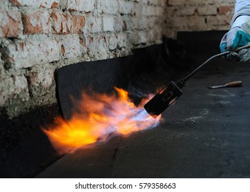 Roofing asphalt bitumen felt installation with heating and melting roll with propane blowtorch during construction works. One torch blowpipes with open flame. Licking flames detail.