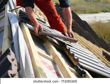 Roofing construction with clay roof tiles. Roofer laying ceramic roof tiles. Lay roof tiles.