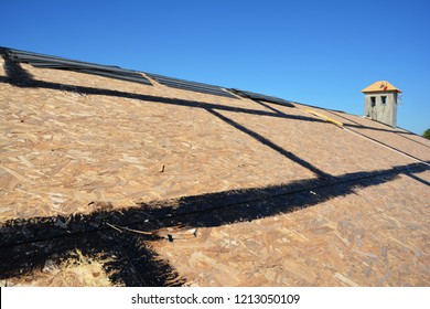 Roofing Construction. Roofing preparation asphalt shingles installing on house construction wooden roof with bitumen spray. Roofing construction. Installing bitumen roof shingles.