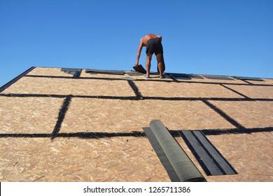 Roofing construction with roofer and asphalt shingles, roofing tiles in his hands. Roofing construction concept.