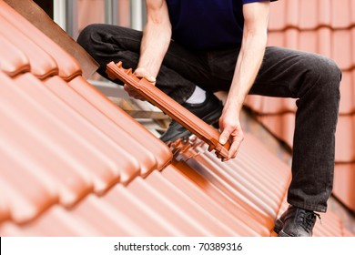 Roofing - construction worker standing on a roof covering it with tiles