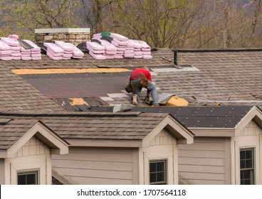 Roofing contractor removing the old tiles before replacing with new shingles on a townhouse roof