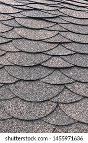 Roofing, made of shingles. Texture of shingles. Vertical photo of soft Shingles tiles. Texture of the soft roof. Background on the topic of roofing construction materials.