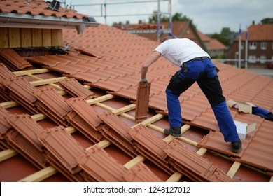 roofing red clay tiles, roofer builder with white t shirt on rooftop of a house and roof construction site