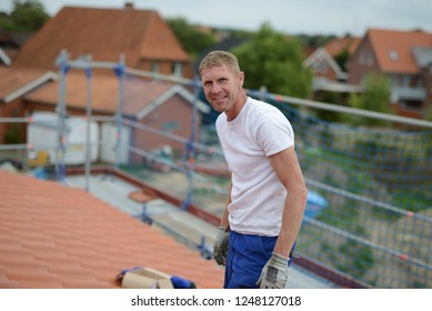 """roofing red tiles, friendly roofer builder """"Handwerker Dach"""" in white t shirt on rooftop of a house and roof construction site"""