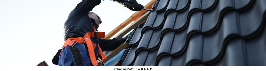 roofing worker on roof repair, working on leaking roof in protective gear with roofer tools