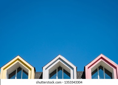 Roofline covered with shingle and pointed attic windows against blue sky with copy space
