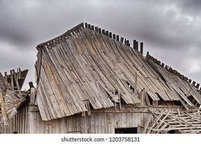 The roofline of an old wood barn whose roof is collapsing is outlined against a dramatic cloudy sky.