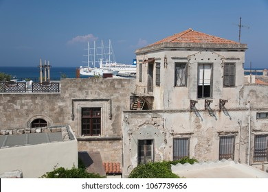 The roofs of buildings in Corfu Greece, summer, afternoon sun, blue sky, sea, ships, urban architecture.