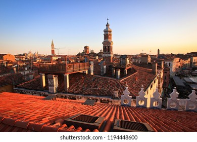 Roofs of houses and the bell tower of Venice at sunset