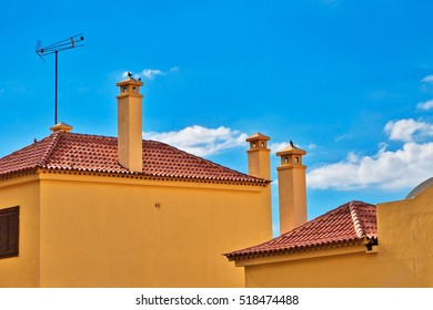 roofs of houses with chimneys on sky background