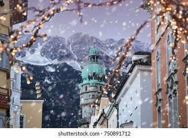 Roofs of Innsbruck with mountains on a background and Christmas lights on a foreground at winter snowy evening
