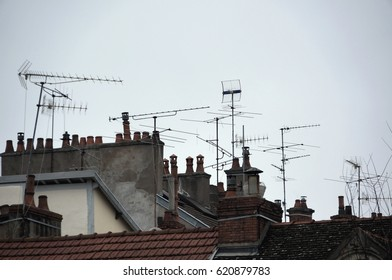 Roofs with many tv antennas. Roof with many chimneys. Smoking chimney. Many tv aerials. Awful city landscape.