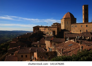 The roofs of the medieval town of Volterra overlook the autumn hills of Tuscany. Satellite dishes, medieval architecture and rustic tiles: epochs mix, just like blue and ochre.