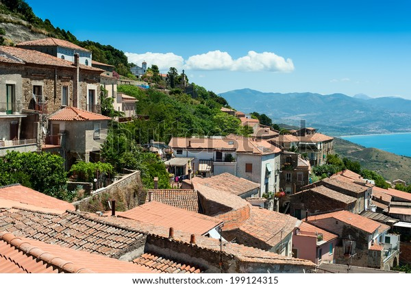 Roofs of old buildings on the hill with sea and mountains on background. This picture was taken in Acciaroli, Cilento park area, Campania, Italy.