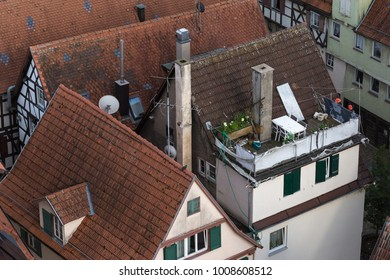 roofs patio and terraces with chemin oven and outdoor furniture on a very sunny day in june in south germany in center of a historical city