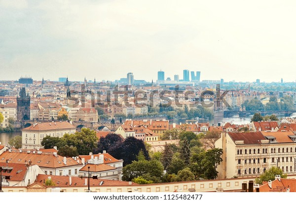 Roofs of Prague, Czech Republic. Scenic spring aerial view of the Old Town and Charles Bridge over Vltava river in the background.