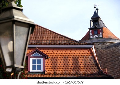 roofs and spire of buildings from the early Middle Ages with a blurred lantern in the foreground,