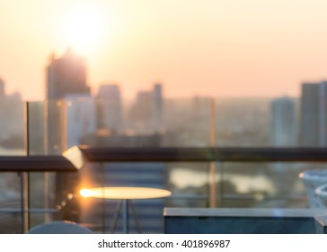 Rooftop bar party blur city view background from hotel balcony toward blurry restaurant dining table during sunset happy hour golden sunset