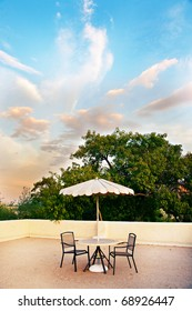 A rooftop getaway at sunset, with a table, two chairs and an umbrella.  Beautiful sky and clouds are in the background