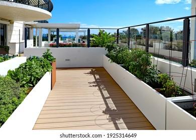 Ein Dachgarten auf einer Außenterrasse in einem Wohnhaus, mit Behältern für die Pflanzen.