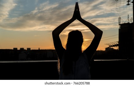 Rooftop meditation silhouette of a woman in sunset