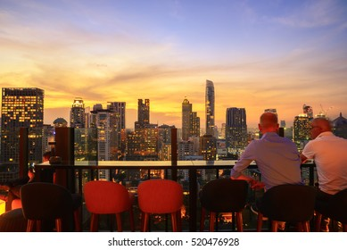 Rooftop open bar view point top view city center at Bangkok. Bangkok city view point  from rooftop bar with blur people movement ,City of light and gold sky background. Business city success industry.
