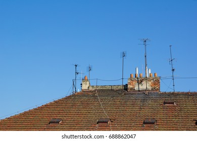 Rooftop with orange roof tiles, antenna, lightning conductor, rod and dormerwindow. Clear blue sky as copy space area