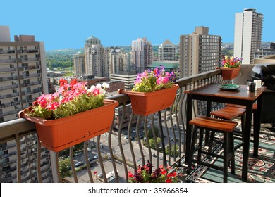 Rooftop patio with table and stool chairs, colorful flower baskets along a balcony railing with Calgary building skyline in the background