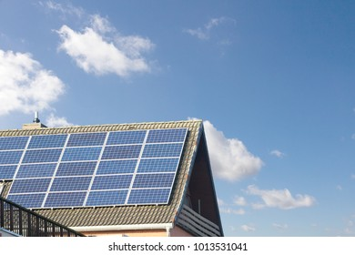 rooftop with solar panels and blue cloudy sky
