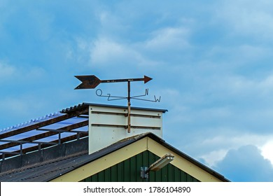 Rooftop of a stable with a weathervane
