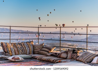 Rooftop terrace decorated with pillows and carpets in Turkish style with the view in the morning over balloons in Göreme from Uçhisar, Cappadocia, Turkey