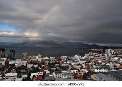 Rooftop view of a rainbow over the city of Reykjavik in autumn