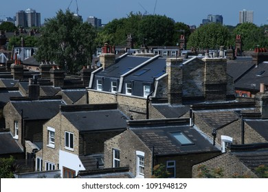 Rooftop view of residential housing in South London, England on a bright sunny day.  Sky is blue and trees are full and green amidst a sea of rooftops with chimneys.