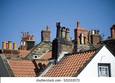 Rooftop view of a variety of different chimney pots on quaint cottages in the fishing village of Robin Hoods Bay, UK