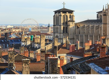 Rooftops, chimneys and cathedral of the old town Vieux Lyon, with ferris wheel in the background. Lyon, France.