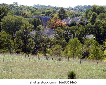 Rooftops of a new housing development seem to be hiding among the trees next to fenced farmland in Southwest Missouri.