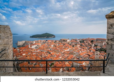 Rooftops of old houses in Dubrovnik, viewed from the Old Town fortified walls with Lokrum Island in the background