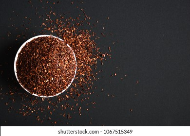 Rooibos tea in a white bowl on a black background. Flat lay, top view, copy space