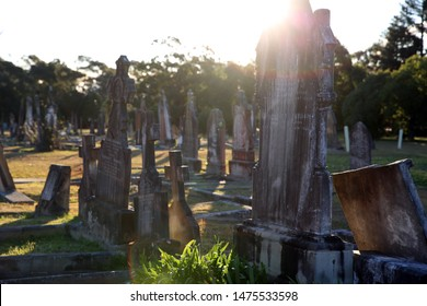 Rookwood, NSW Australia - August 11, 2019 - gravestones at Sydney's largest and oldest working cemetery - gravestones at sunset - lens flare