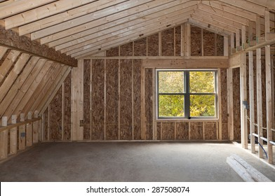 Room addition construction with pitched ceiling and autumn trees view window