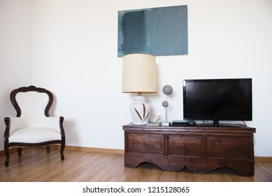 Room with armchair, tv, lamp and white wall. Abstract accommodation. Minimalism in lodging.