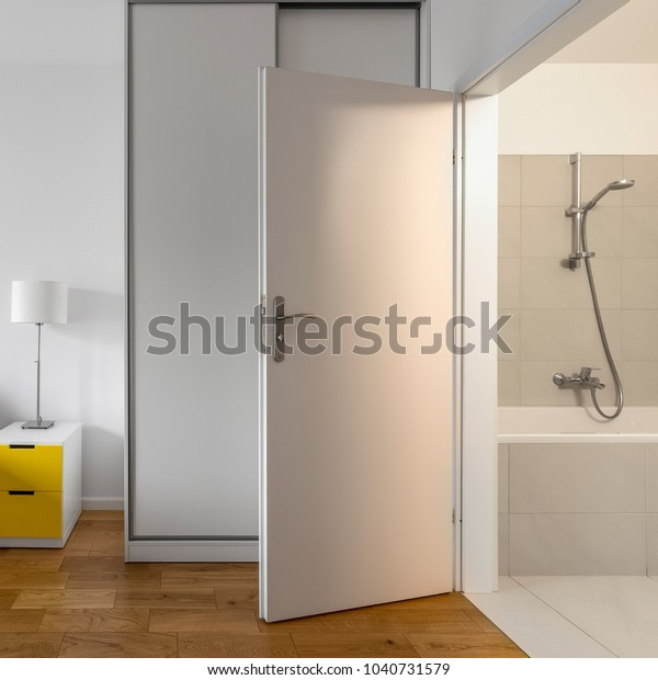 Room with bathroom, wooden floor panels and yellow side table