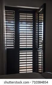 A room with a bed and an open door to the balcony on the background of closed wooden blinds