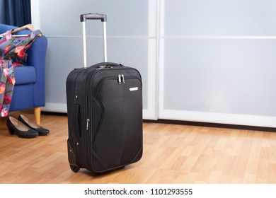 Room with black packed roller suitcase in front of closet