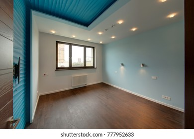 The room with blue walls and a big brown window